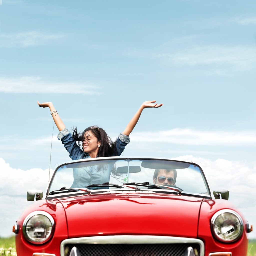 A couple enjoying their summer holidays and a road trip in a red convertible