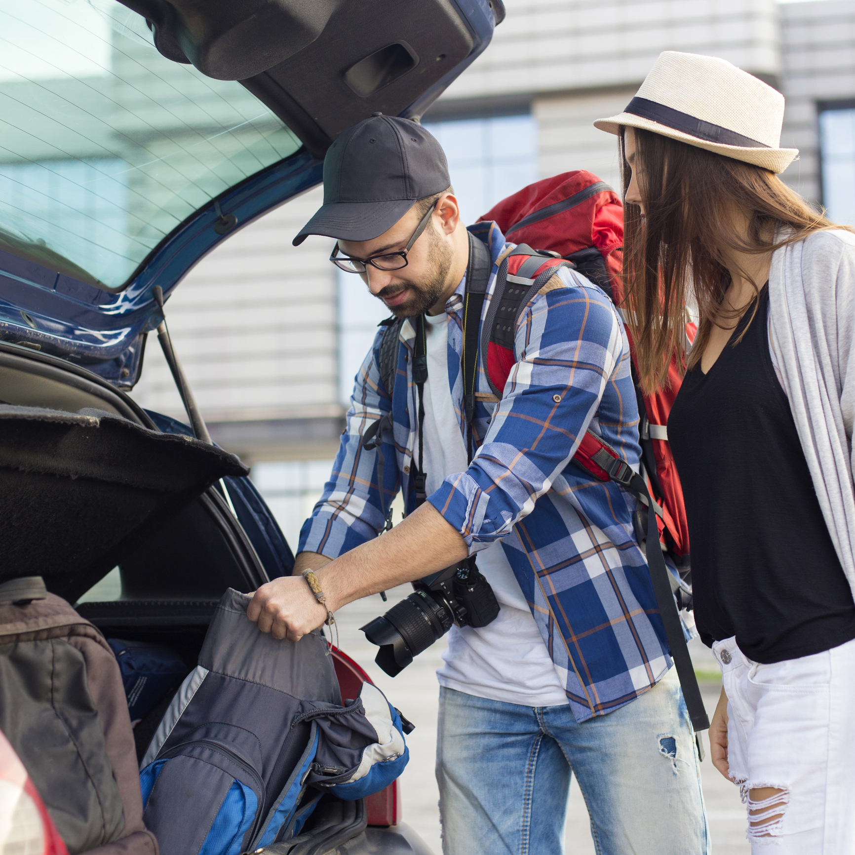 A couple with backpacks unloading their car, ready to head on their holiday