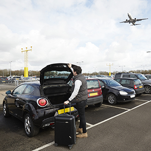 A man closing his boot in Gatwick Airports Long Stay car park whilst a plane flies overhead